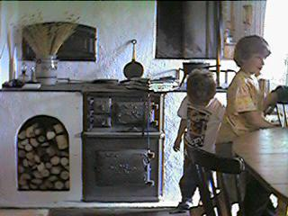 The woodburner in the kitchen in the big house at Svinnersta, with added Conor and Ebba