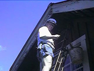 Gunnar up a ladder painting the big house